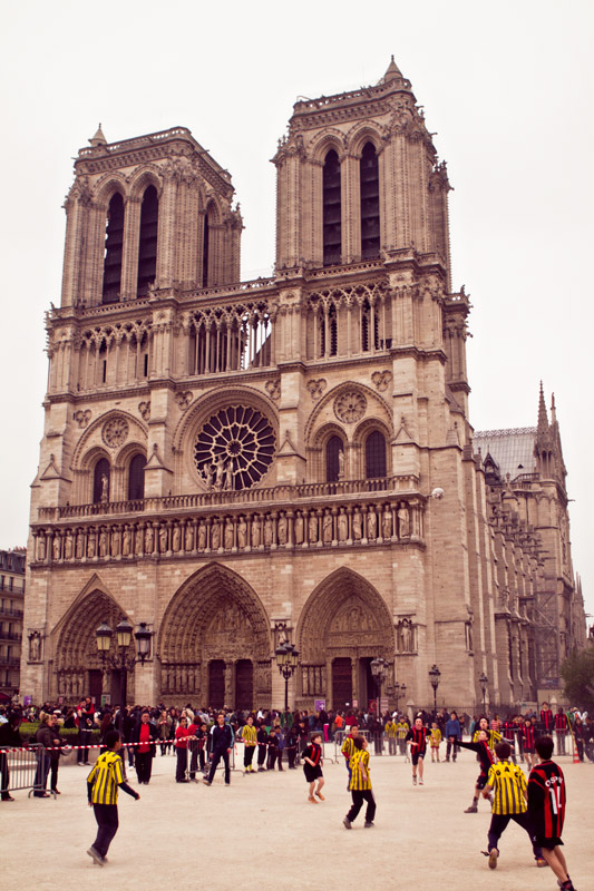 Kids playing soccer outside of Notre Dame Cathedral